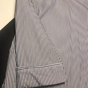 Blå og hvid stribet bluse med sjov detalje nederst på ærmer.