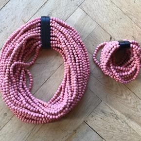 Halskæde og matchende armbånd i lyserøde træperler med magnetlås. Længde halskæde: 43 cm. Længde armbånd: 19 cm.  Aldrig brugt.  Bud modtages.