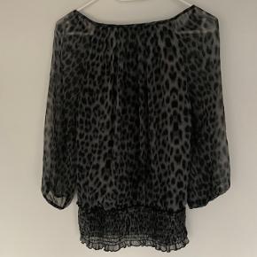 Elegant langærmet bluse i leopard mønster. Ærmerne er i meget tyndt stof, hvilket gør blusen lettere at se på og have på. Fin detalje nederst på blusen. Blusen har et sort stof indvendigt fra brystet og ned, så den ikke er gennemsigtig, som på ærmerne. Fejler intet.