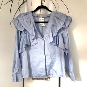 Fin blå skjorte men detaljer fra H&M str 40. Aldrig brugt om med prismærke. Nypris 350.
