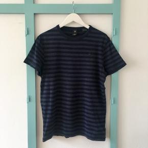 T-shirten er blåstribet, lidt tyk i stoffet, blød og i god stand. Passer også en L rigtig fint.