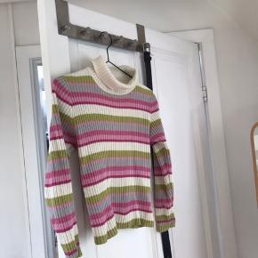 Fin stribet strik i forskellige nuancer af hvid, grøn, lyserød og lilla. Passer bedst en petite størrelse, så det skal man lige have in mente. Strikken har også rullekrave