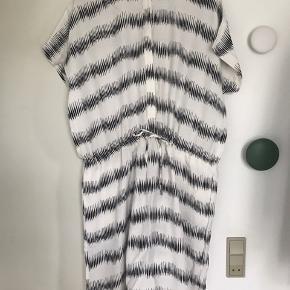 Fin knælang kjole (går mig til lige under knæet, er 170 cm).  Lille løst ærme, bindebånd i taljen og knapper fortil.