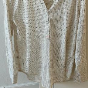 Fin hvid skjorte med sorte prikker. Brugt men i god stand.