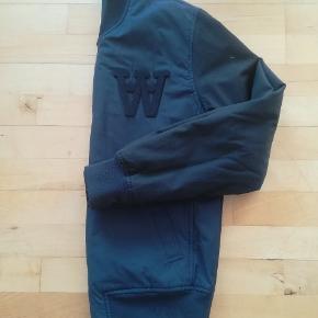 Jakken er blå med sorte ærmer. Det er en drenge/herre model. Den måler 44 cm over skuldrene og længden i ryggen er 67 cm med ribkanter.