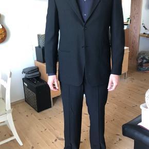 """Virkelig flot og stilig jakkesæt, som desværre bare ikke bliver brugt.  Jakke, skjorte og bukser i flot stand. Der er tynde skulderpuder i jakken, og pressefold på bukserne. """"Modellen"""" er 185 høj, bruger normalt L. Skræddersyet.   Blev købt via en fundraising på tv for en 5-6 år siden, da sættet har været båret af en kendt (husker ikke hvem, desværre). Har kun været brugt til én tv-optræden og ét privat arrangement.   Sendes ikke, men kan afleveres i det meste af  Djursland (Århus og Randers) området uden merpris."""