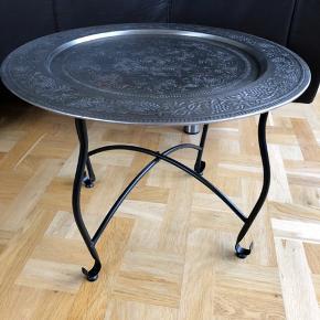 """Lille rundt bord med sorte metal ben og en mønstret metal bordplade. Bordpladen kan tages af og bruges som """"bakke"""". Det er i god stand bortset fra lidt rust på bordpladen (der er vedlagt et billede)."""