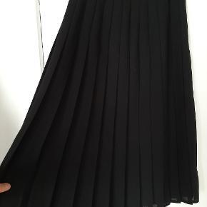 Flot lang plisseret nederdel med høj talje og underskørt. Den har lynlås i siden i taljen.   Der er ikke noget mærke med størrelse, men vil sige at det er en størrelse small (taljemål ca 70 cm).