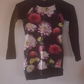 Flot trøje/tunika med stort blomster mønster foran, sort bagpå. Kanten i bunden har skråt snit.   Se også mine andre annoncer med tøj i samme størrelse.