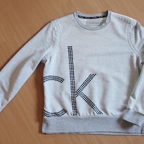Lysegrå sweatshirt fra Calvin Klein, str. M. Længde 57 cm, brystvidde 104 cm. 60% bomuld, 40% polyester. Vasket 1 gang, aldrig brugt. Sælges for 250 kr. pp