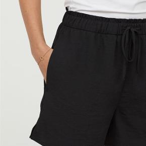 CONSCIOUS. Korte shorts i crepet, vævet kvalitet med elastik og snøre i taljen samt lommer i sidesømmen. Shortsene er delvist fremstillet af genvundet polyester. Polyester 100%  Korte shorts i crepet, vævet kvalitet med elastik og snøre i taljen samt lommer Farve: Sort Oprindelig købspris: 129 kr.