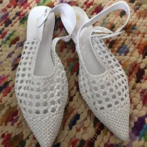 Fine hvide slippers med rem bagtil fra H&M. Aldrig brugt, idet de desværre er for små.   MP 100 kr. pp.