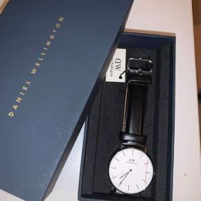 Daniel Wellington ur med sort rem   Der er en lille gravering på bagsiden