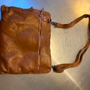 Super fed taske fra Cph Adax - købt i Salling - aldrig brugt. Vasket cognacfarvet kernelæder og med plads til en iPad. Skindet har medfødte skønshedsfejl som en del af taskens look. For et mere feminint udtryk kan man vælge en anden taskerem. To indvendige rum. Størrelse ca. 34x27 cm.