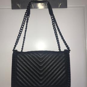 Sort vatteret taske med kæderem.  Kan fungerer både som cross-body, skuldertaske eller håndtaske, da man kan bruge remmen enkelt eller dobbelt.  Kæden er lidt tung, men rigtig flot taske, jeg får den bare ikke brugt. Den er købt i december, og pristagget er fjernet, men står fuldstændig som ny.
