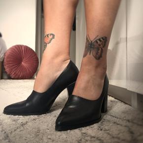 Bianco spidse pumps i sort læder med 8 cm chunky hæl. Str 37, men passer en 38. Et par fede men sofistikerede sko der virkelig sidder godt, med en karakteristisk lige overskæring over foden. Brugt få gange og i ingen tegn på brug på oversiden. Dog kan der i det stærkt lys ses trykmærker bag på hælen og der er en lille ridse på indersiden af den ene hæl (som dog kun ses når man vender skoen).