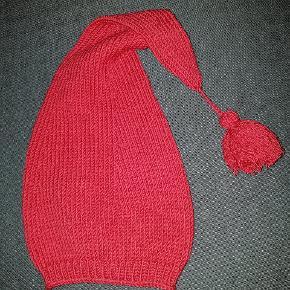 Nissehue rød Merinould 100% kradsefri. Maskinvask v 40 grader. Str 6-12 mdr. Bemærk den gode længde på huen! Se også mine andre nissehuer i grå, i andre størrelser