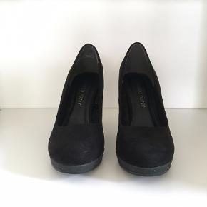 Flotte, klassiske sko fra Marco Tozzi. Sorte, hæl og plateau i sort glimmer.  Gode at gå i. Sælger, fordi jeg desværre ikke kan passe dem længere.  De er overordnede i rigtig flot stand, men har været brugt en håndfuld gange, og har derfor nogle brugsspor. Der er et lille afslag i glimmeret på den ene plateau sål, og en ridse i det sorte ved den ene hæl. Kan sagtens sende flere billeder :)