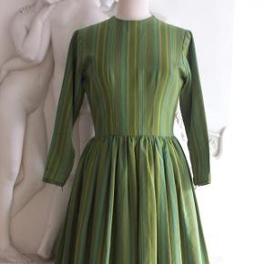 Vintage Kjole / retro kjole fra de tidlige i 1960ere.  Sælges, da den desværre er for lille til mig 😞  Enkelt kjoleliv med høj rund halsudskæring. Rynket knælangt skørt med masser af vidde. Lange, tætte ærmer med plastiklynlås ved håndledet. Lukkes med metallynlås i ryggen. Kjolen er syet af kraftigt grønt bomuldsstof med grønne, blå, gule og lyserøde striber.  Stand: Ingen synlige pletter eller andre fejl.  Mål:  Bryst: 96 cm  Talje: 79 cm  Hofte: fri  Længde, skulder til bund: 106cm  Skulderbredde 42 cm:  Ærmelængde, armhule til håndled: 44 cm