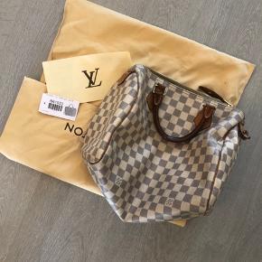 """Jeg overvejer at sælge min fine Louis Vuitton speedy 30 damier azur taske. Tasken er fra 2011, men i fin stand. """"Plastikket"""" i lommen er lidt slidt af (se billede), nøglen er desværre tabt og æsken er gået i stykker, men pose og original kvittering haves. Jeg er åben for realistiske bud 🙂 mødes gerne for at handle"""