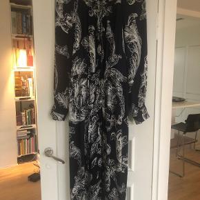 """Smuk, let """"silkeagtig"""" kjole. Købt i sommeren 2019 i anledning af et bryllup. Den er virkelig dejlig at have på, fordi den er så let i stoffet. Desuden en fin detalje med skjulte lommer. Den er brugt ialt 3 gange. STØRRELSEN er angivet til en S, men selv er jeg en str. 42. Den er med bindebånd i livet og kan snørres tæt + udvides en del. Derfor skriver jeg one size. Jeg gav 2500 kr. for den og sælger den til under halv pris. Sender gerne på købers regning."""
