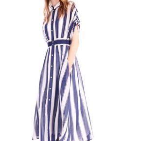 Bomulds crepe kjole i to-tonet strib. Skjortekjolen har knapper foran og i let og luftig kvalitet. Der medfølger hvid underkjole med stropper, som er revnet lidt i en syning. Mærket med str angivelse er klippet af. Jeg er en 38/40 og passer denne. Pris i butikkerne nu er 3400