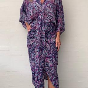 Sissel Edelbo kjole Style: Juno dress kjole  Farve: Multifarvet  Størrelse: S/M Købspris: 999,-  Super flot og feminin kjole fra Sissel Edelbo Ny og stadigvæk med prismærke 🌸💞🌸  Utrolig smuk kjole med brede løse sommerfuglærmer for et afslappet og bohemian look. Silhuetten er løs, men takket være den lagdelte samling i taljen bringer den facon til kjolen. Den er meget smuk og perfekt på alle kropstyper. Den fremhæver på bedste vis de kvindelige former, og den har et feminint og elegant look.  Kjolen er ideel til både hverdag og fest. Det feminine og alligevel enkle udtryk gør kjolen perfekt til en dag i solskinnet med et par sandaler eller sneakers. Den smukke lagdelte samling på taljen gør også kjolen let at style til en aften ude med høje hæle og røde læber for et festligt look.  Kjolen er lavet af genanvendte sarier. Alle sarier er håndplukkede af Sissel Edelbo, og er, før de blev re-designet, blevet båret af en indisk kvinde. Kvindens og sariens historie viser sig i de unikke mønstre og små karakteristika. Ved at bære denne smukke Juno kjole fra Sissel Edelbo fortæller du historien videre.  Sissel Edelbos produkter er lavet af vintage sarier. Da stoffet er genanvendt, kender vi ikke den totale sammensætning af stoffet, som er håndplukket i Indien som en silke-mix. Der kan af samme grund forekomme små fejl i stoffet. Den er købt på tilbud, så der er lavet et mærke i tags i nakken. De små fejl er en del af sariens charme og historie og betragtes ikke som reklamation.  Alle produkter fra Sissel Edelbo er unikke.  Dvs der kun findes den ene du ser her på billedet, og kun i den viste størrelse.  Dét gør din kjole helt unik - og et smukt og farverigt alternativ til andre kjoler.  LET THE STORY CONTINUE - FROM ONE WOMAN TO ANOTHER💞🌸💞