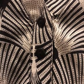 Lækker 100 % viskose bluse i sort / hvid print  M ( 46/48 )   Den er uden Gozzip mærke i nakken