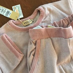 Nyt Lækkert blødt sæt med velourkanter.  Blusen har korte 3/4 ærmer.  Bukserne har regulerbar talje.  Rosa.  Str. 8.  Købspris 380,-