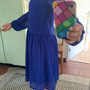 Smuk blå kjole i str s, men passes også af m. Løs model. Med underkjole indsyet, og gennemsigtige ærmer og over brystet. Kun brugt 2 gange. 107 cm lang.