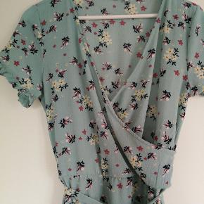 Fin sommerkjole i turkis/lyseblå med blomster og bindebånd. Kun brugt 1 gang og fejler intet. Strs small med elastik i livet.