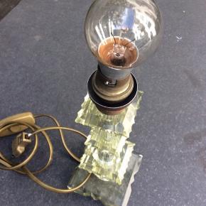 Fin mindre bord lampe  i krystal glas. Fransk oprindelse , købt i fil de fer antique.  Lampen har en ledning med tænd / sluk og bruger en ældre slags pære.  26 cm høj, bunden er 9 cm bred. Ingen fejl.   Nice and small glass CRYSTAL lamp ,  French from antique shop I Cph.  Has no cracks , good condition, for electrical use.  Size is: 26 high, 9 cm feet.