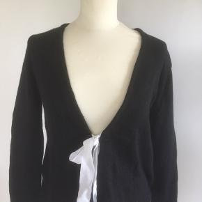 Mærke: H&M Størrelse: XS, passer også str S Farve: sort Materiale: 30% Angora og 70% polyamid Trøjen: længde 55 cm og bryst mål er ca. 96 cm. En blød trøje med V udskæring, bindebånd og hulmønster nederst på trøjen Stand: brugt få gange  Sælges kr 50 Bytter ikke Sætter pris på tilfredse købere
