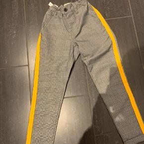 Bukserne er ternet med en gul stribe langs benet