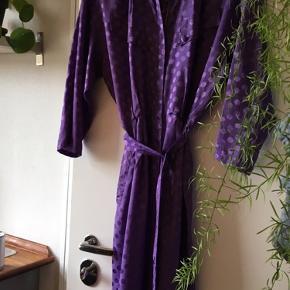 Fantastisk, violet dragt med flotte detaljer, mønster og shine i.  Den har to flotte brystlommer, lynlås fortil og bælte med flot stropdetalje bagtil. Der er også sidelommer i.   Den vejer ingenting og er derfor ekstrem let og behagelig at have på.  Den er str. 38 og vasket på 30 grader.   Obs: Der er en mindre syningen fortil, der skal have et par sting.   Den er købt vintage i Amsterdam!   Flere fotos kan tilsendes!