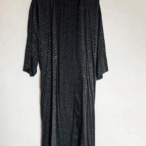 Flot kimono i zebramønster (sort på sort, blank/mat effekt). Passer en 36/38. Har bindebælte og kan bruges åben over fx jeans eller leggings men kan også bruges som kjole med det tilhørende bælte. Brugt 1 gang og er som ny. Bytter ikke.