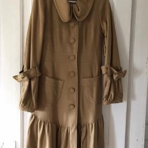 Flot lun frakke med fine detaljer så som sløjfer på ærmerne og fine læg nederst på frakken. Kun brugt en gang. Jeg tager ikke billeder med tøjet på