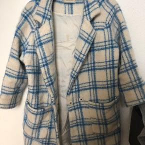 Uldfrakke fra Ganni (WS 14/15). 60% uld.   Tydelig brugsspor indvendig i form af pletter. Kan fjernes ved rens. Ingen yderligere brugsspor.   KAN PASSES af både xs - s - lille m.
