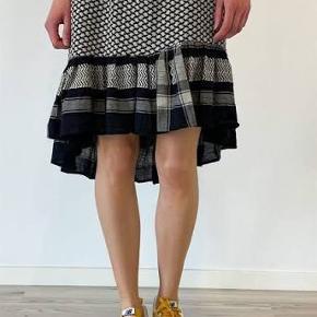 Fineste nederdel fra Cecilie Copenhagen.  Nederdelen har det velkendte mønster og i sorte og råhvide farver. Den har et bredt elastik i taljen, og den er længere bagtil end foran.  Nypris 999kr.