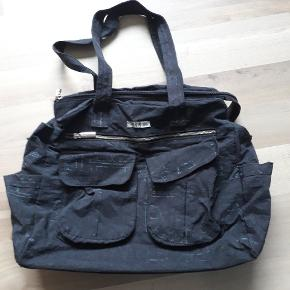 Stor rummelig sort taske med rigtig mange lommer. Mønstret (biler) er utydeligt og der mangler skulderrem, derfor den lave pris.