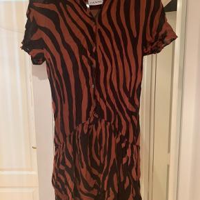 Stribet kjole fra Ganni i rustrøde og sorte farver. Kjolen er brug og bærer tegn af dette i form af nogle trådudtrækninger (dette afspejles også i prisen). Kjolen har et lag øverst, hvilket gør den lidt gennemsigtig. Nederst omkring hoften er der 2 lag, så her kan man ikke se igennem.
