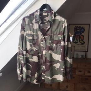 """Fin camouflage skjorte i 100% bomuld. Stadig super flot! Har lidt """"pletter"""" foran forneden, men ikke noget man lægger mærke til - synes bare jeg ville nævne det. (Billede 3)  Desuden er de fleste af stenene i hjertet (logo) bagpå gået af, men det betyder jo intet for helhedsindtrykket! 😊"""