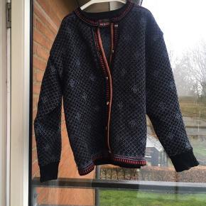 Flot og meget velholdt norsk retro cardigan / sweater / strik i 100 % uld. Flot mønster og søde hjerteformede knapper. Den er uden pletter og huller. Der står XL men den svarer til en M i størrelsen