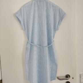 Sød skjorte kjole i lyseblå med hvid. Gennem knappet og med bindebånd om livet. Kan bruges som kjole og udover buks.