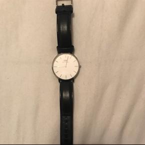 Sælger dette Daniel Wellington ur med sort læderrem og sølv urskive. Der er ingen tydelige tegn på slid og brugt meget få gange.