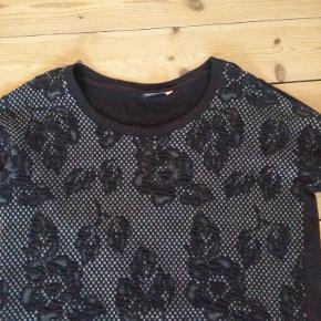 Fintstrikket sort trøje med grå-sort blomstermønster på forsiden. 88% bomuld/8% polyester/4% viskose. Kun brugt et par gange.  Mål Længde: 68cm Bredde: 57cm