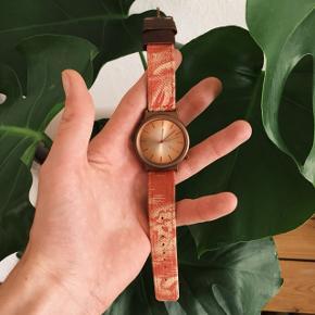 """Komono ur i bronze med rød rem  • Bud er velkomne og jeg sender gerne •   - Selve uret er lavet i børstet stål med en bronze finish - Skivens diameter er: 3,6cm  - Remmen har et rødt """"Hawaii"""" mønster og har detaljer i ægte læder - Uret er næsten ubrugt - Original prisen: 450kr"""