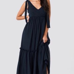 Smuk sort kjole fra Gestuz. Kjolen har smuk v-udskæring på for- og bagsiden, fine bindebånd som stropper, og har desuden den fineste flæse-effekt for neden. Perfekt til enhver festlig anledning. Stadig med prismærke og aldrig brugt.