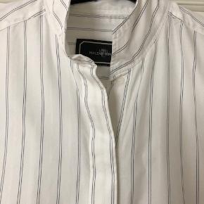 Skjorte i 100% bomuld. har stribeeffekt i farverne sort og hvid.  Mål: Længde 84 cm foran 90 cm bagpå Bryst 2 x 57 cm