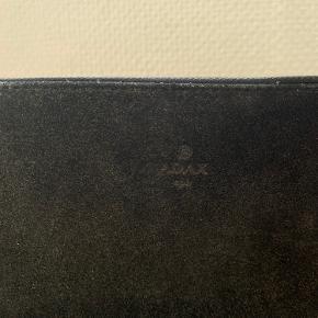 Adax taske, i ruskind, med to store rum. Remmen er købt seperat og fra et andet mærke, men ikke noget man bemærker